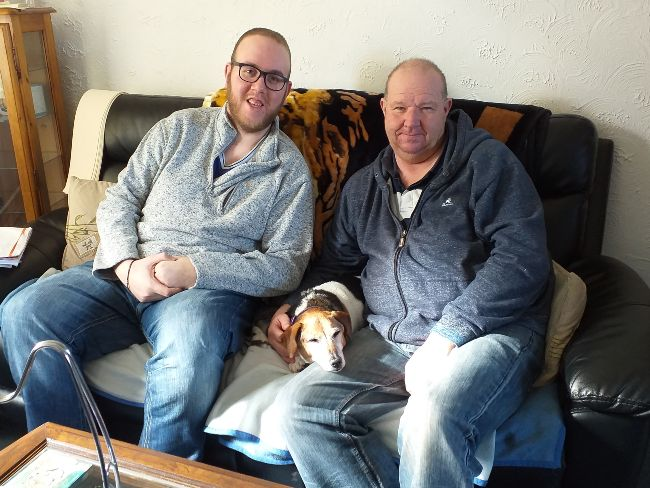 Two men sat on a sofa with a dog