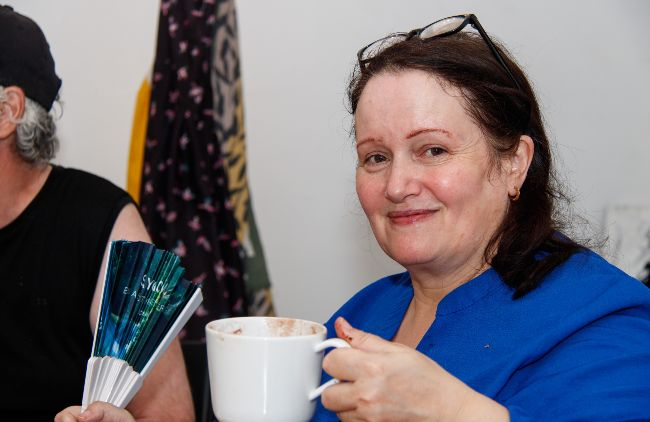 Lady smiling, with cup of tea