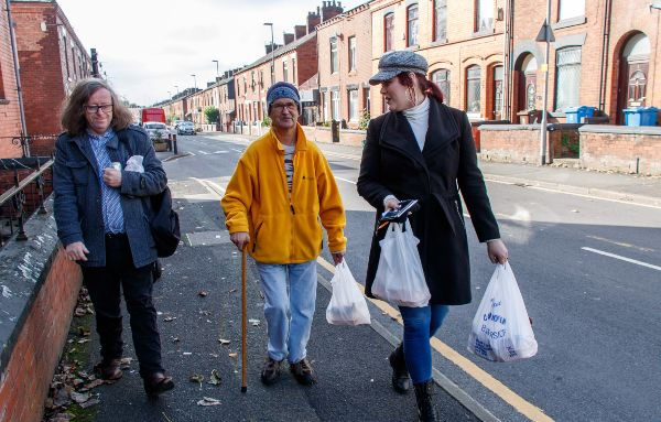 Three people walking down the street together with carrier bags