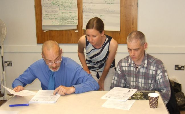 Two men sitting at a table looking at documents, with a woman looking over them.