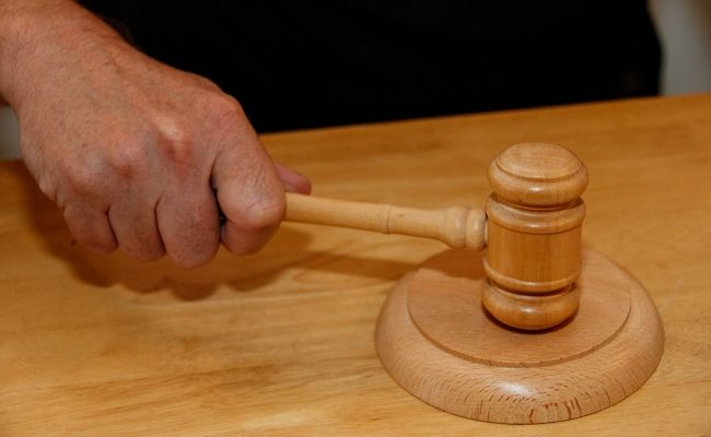 A hand on a wooden gavel