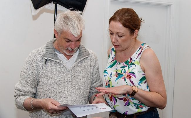 A man and a woman looking at paperwork together