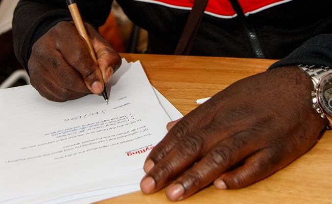 A close up of someone's hands signing paperwork