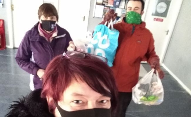 Two people holding shopping bags with a woman in front taking the selfie. Everyone is wearing a mask.