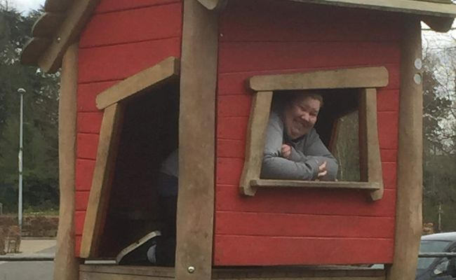 A photo of a woman in a wooden playhouse. She is looking out of the window and smiling.