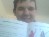 A screenshot of a man on a zoom call holding an open booklet about human rights