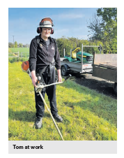 A photo of a man outdoors using a strimmer. The caption says 'Tom is strimming again'.