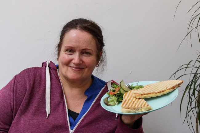 A photo of a smiling woman holding a plate with a panini and salad on it
